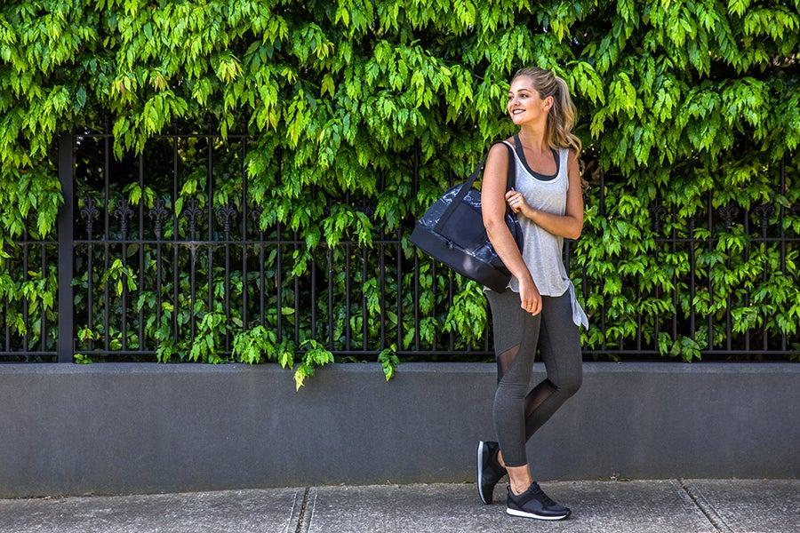 Girl walking through street against green hedge