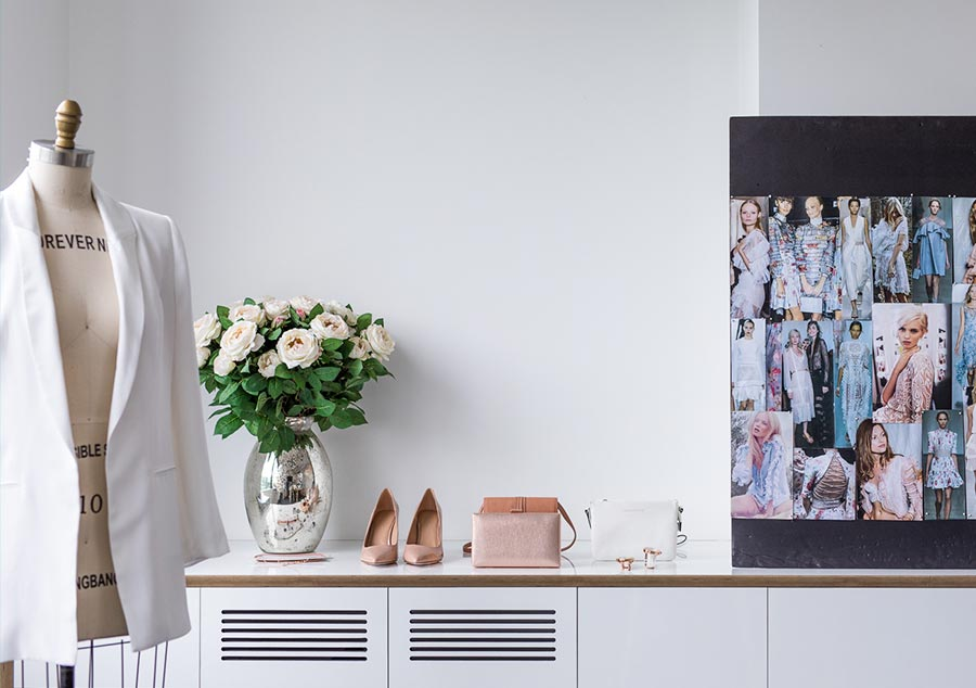 Mannequin and flowers in a room with moodboard and white jacket