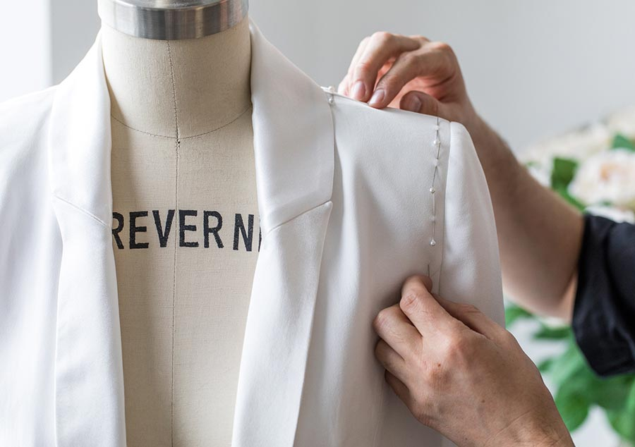 Person pinning sleeve on garment on mannequin